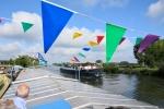 Feestelijke vlaggen op het dek, een passagiersschip vaart voorbij