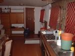 Rechts de keuken, midden het toegangsluik naar het achterronder en op de achtergrond de deur naar de slaapkamer