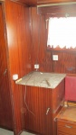 Hoekkast met marmeren blad. Rechts een stuk van de zitbank.